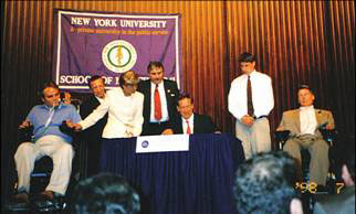 Governor Pataki signing into law legislation to establish a Spinal Cord Injury Research Board and Trust Fund, July 14, 1998. Joining the Governor are (left to right) Officer Steven McDonald, NYPD; Assemblyman Samuel Colman; Mrs. Steven McDonald; Paul Richter, NYS Police Sergeant (Ret.)and also NYS Coordinator, Spinal Cord Society; Matthew Reeve and his Father Christopher Reeve.